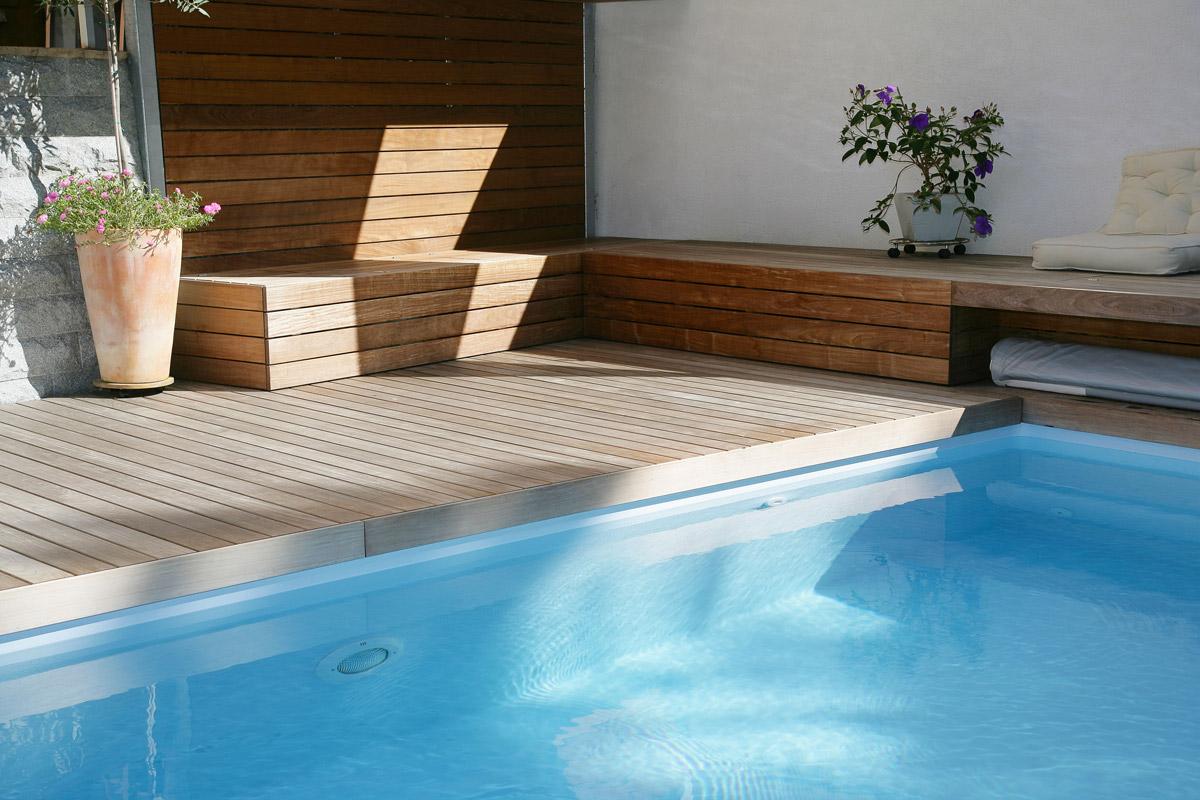Holzbank und Terrasse als optische Einheit für den Pool